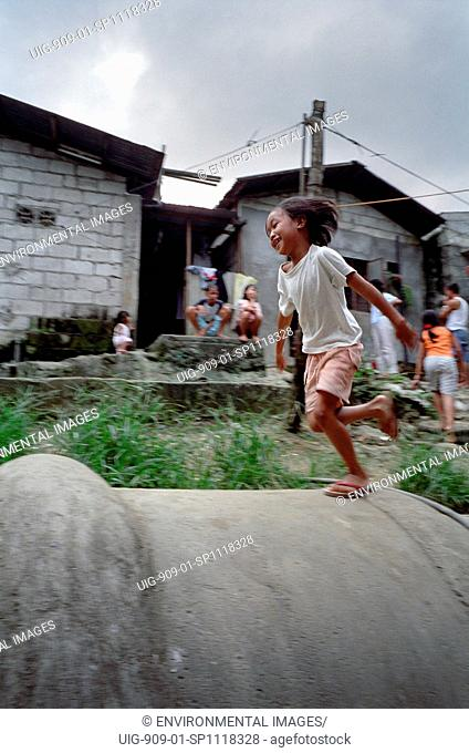 WATER AND SANITATION, PHILIPPINES. Manila. Payatas landfill site. . Children playing on main drainage pipe installed as part of an extensive scheme to improve...