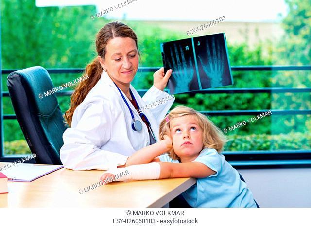 female pediatrician in white lab coat examined little girl