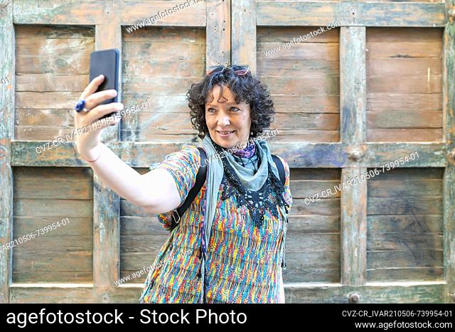 modern middle-aged woman taking a photo from her smartphone
