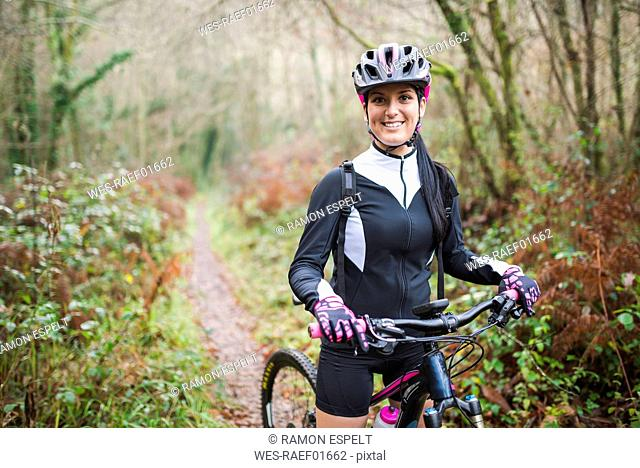 Portrait of smiling woman with mountain bike in forest