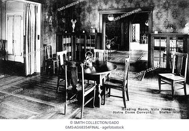 A postcard from a photograph of the reading room in Villa Josepha which was part of the Notre Dame Convent; the room is modestly decorated with a table with...