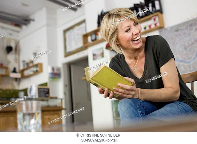 Mid adult woman holding book, laughing