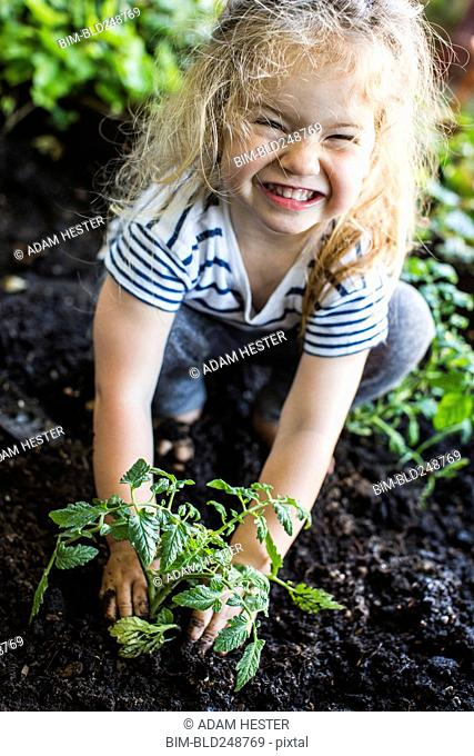 Caucasian girl posing with plant in garden