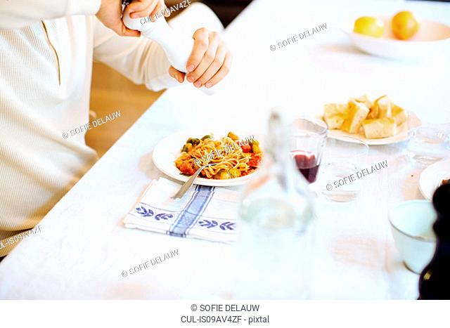 Young mans hands using pepper grinder on spaghetti at table