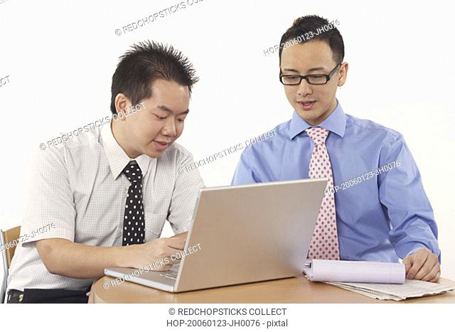 Close-up of two businessmen sitting in front of a laptop