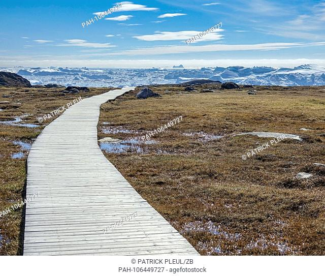 22.06.2018, Gronland, Denmark: A wooden boardwalk leads to the sea near the coastal town of Ilulissat in western Greenland