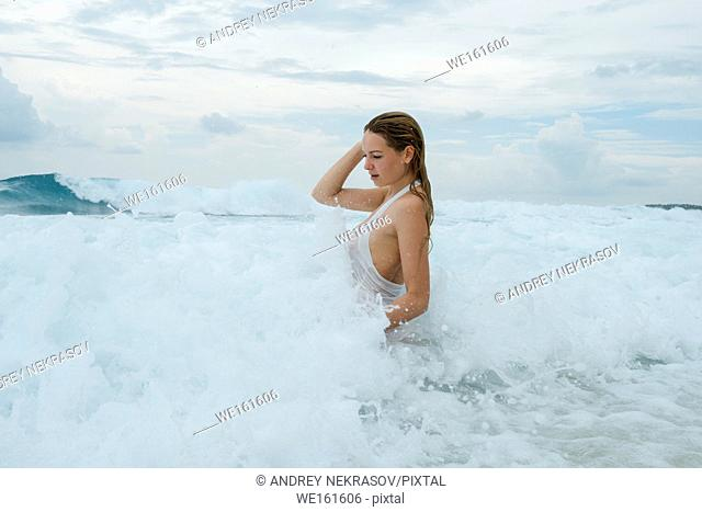 Young woman in a white shirt is bathed in the ocean. Fuvahmulah island, Indian Ocean, Maldives, Asia