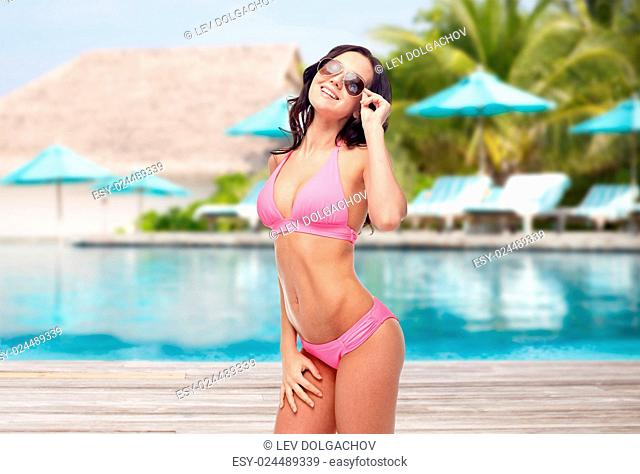 people, travel, tourism, swimwear and summer holidays concept - happy young woman in sunglasses and pink swimsuit over swimming pool and sunbeds at exotic hotel...
