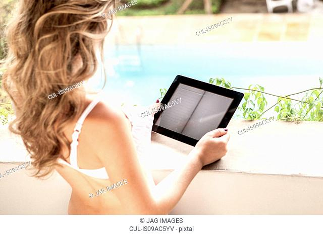 Young woman in bikini top, using digital tablet