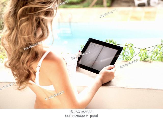 Young woman in bikini top, using digital tablet