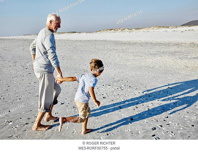 Grandfather and grandson strolling on the beach