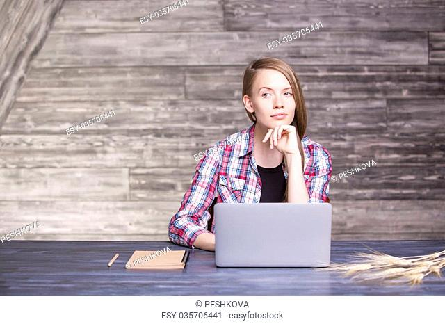 Thoughtful female in casual shirt and with pencil in hand sitting at wooden desk with laptop, notepad and wheat spikes