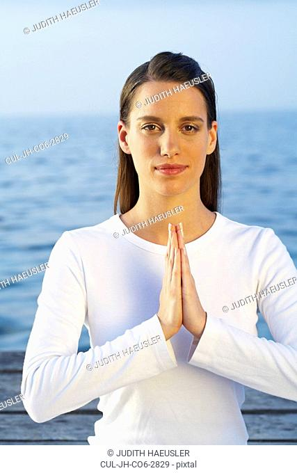 Young woman doing yoga on dock by the sea