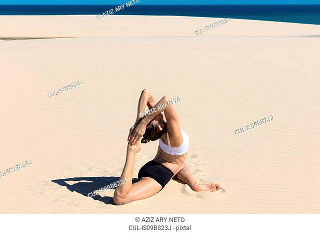 Side view of woman on beach in yoga position, stretching