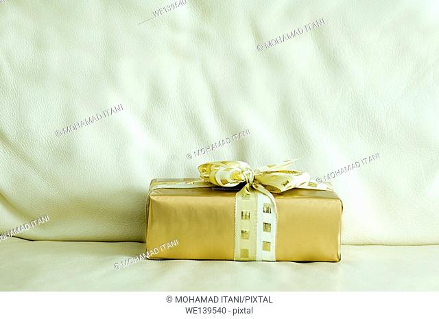 Golden gift box on a leather sofa