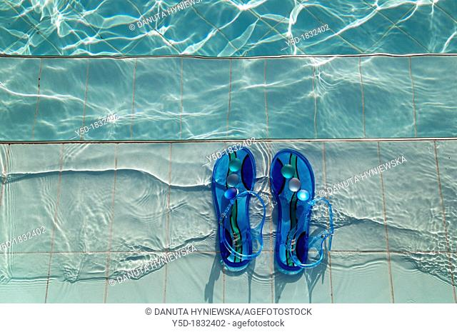 pair of female blue sandals left on the stairs leading to the swimming pool