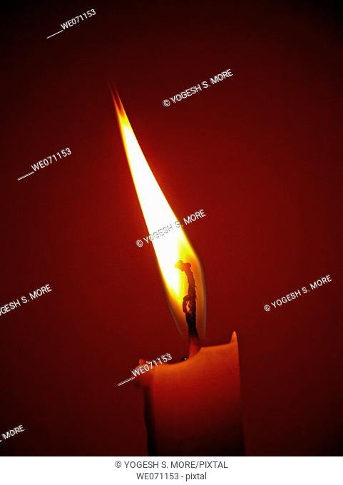 Flame of a candle in the darkness