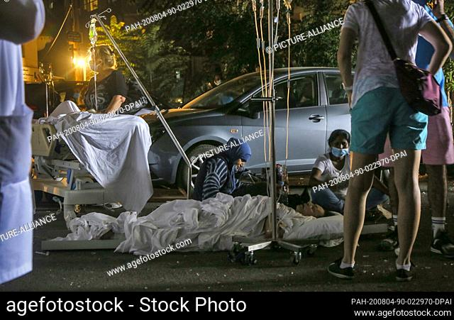 04 August 2020, Lebanon, Beirut: Wounded people wait for treatment at the parking lot of Al Roum Hospital, following a a massive explosion in Beirut's port