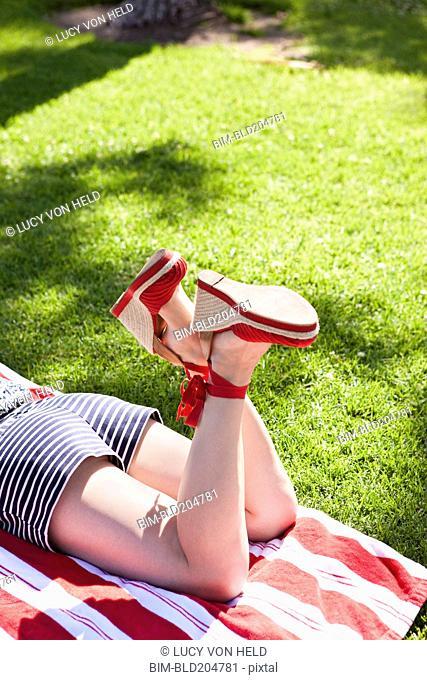 Caucasian woman in heels sunbathing in grass