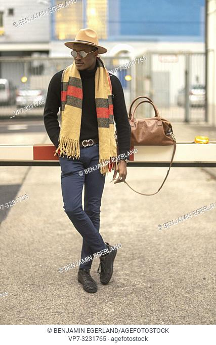 men's fashion blogger Buckman, aka sir bucks, classy man with stylish casual men's fashion outfit, at barrier at industrial area in Munich, Germany