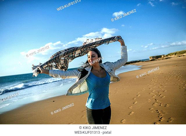 Young woman with blanket in the wind on the beach