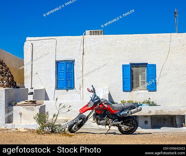 Greece. Oia town on the island of Santorini. Red motorcycle in front of the house