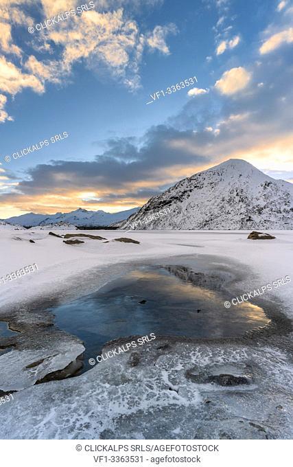 Clouds reflected in the frozen lake Montespluga, Chiavenna Valley, Sondrio province, Valtellina, Lombardy, Italy