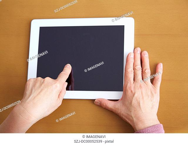 60's woman's hands touching a tablet PC