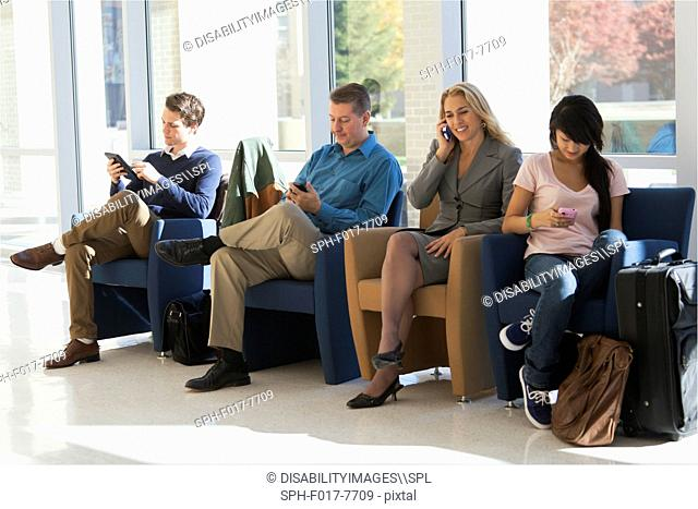 Passengers seated in an airport lounge all using electronics