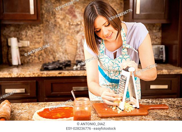 Attractive brunette in an apron grating some cheese and adding it to a pizza in the kitchen