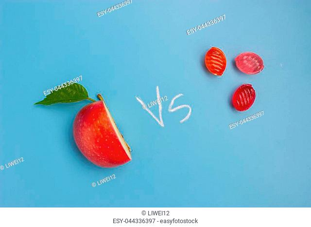 half of an apple and sweet food. unhealthy vs healthy food