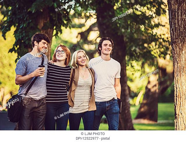 A group of four friends walk closely together arm in arm down a path while talking and laughing on a university campus; Edmonton, Alberta, Canada