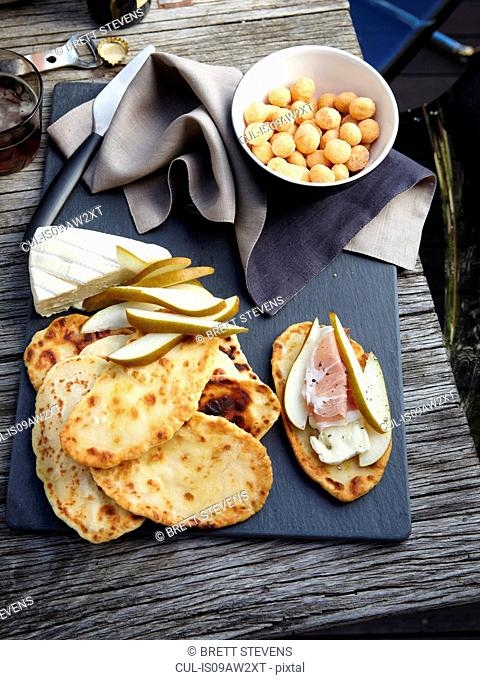 Overhead view of flat breads, taleggio, sliced pears, prosciutto and macadamias