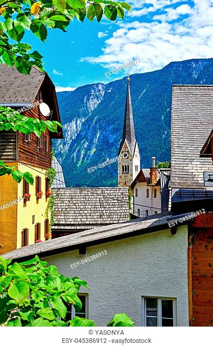 Hallstatt, Austria. Traditional houses and old roofs with view to mountains and broach of chapel of church at coast of lake Hallstattersee among austrian Alps