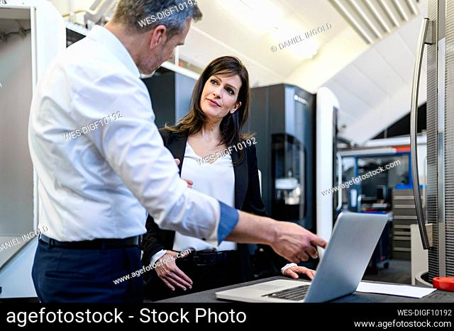 Businessman and businesswoman with laptop having a work meeting in a factory