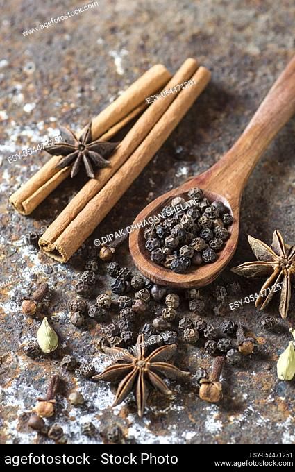 Spices and herbs. Food and cuisine ingredients. Cinnamon sticks, anise stars, black peppercorns and cardamom on a textured background
