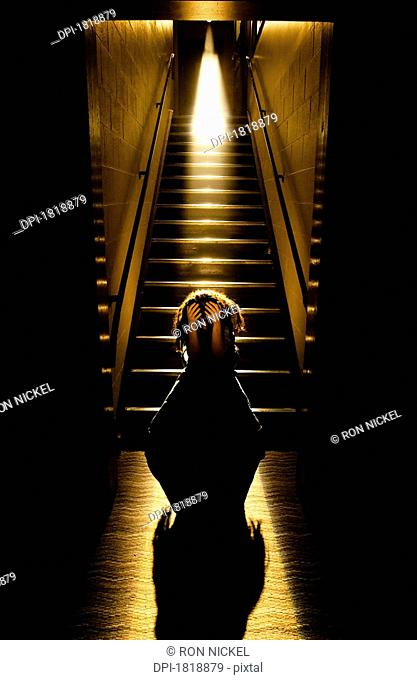 Depressed girl in stairwell with light streaming in