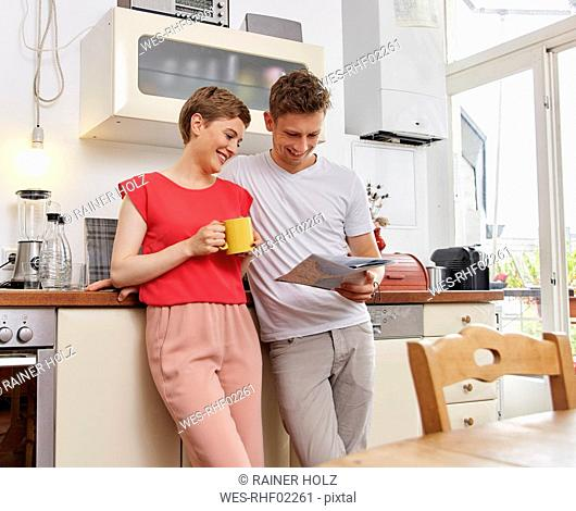 Happy couple at home looking at map