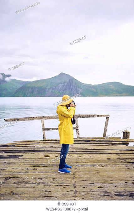 Norway, Senja, man standing on a ramshackle jetty at the coast taking a picture