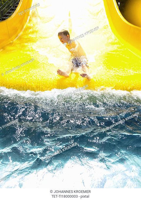 Boy (6-7) having fun on water slide