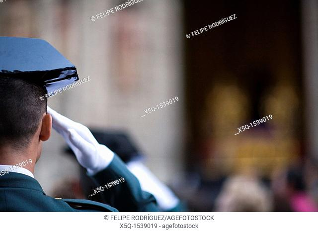 A Civil Guard saluting while a Holy Week procession, Seville, Spain