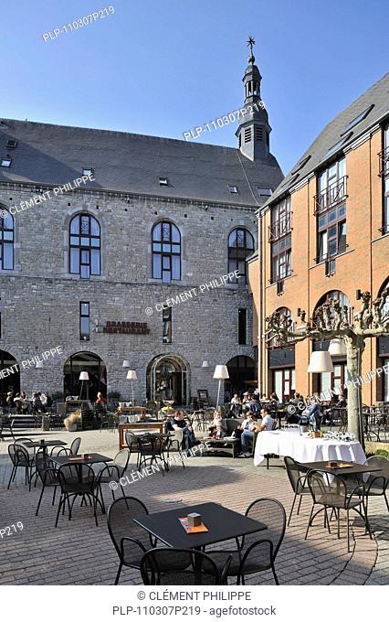 Tourists on terrace of the hotel Quartier Latin, established in an authentic, 18th century Jesuit church at Marche-en-Famenne, Ardennes, Belgium