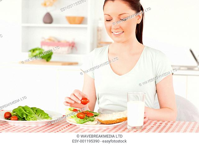 Pretty woman ready to eat a sandwich for lunch in her kitchen