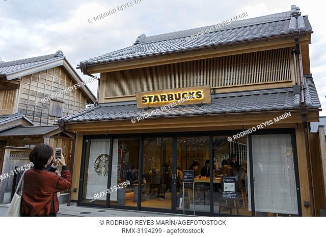 December 5, 2018, Saitama, Japan - A woman takes a picture of a Starbucks coffee shop in Kawagoe. The branch opened last March is located near to the Toki no...