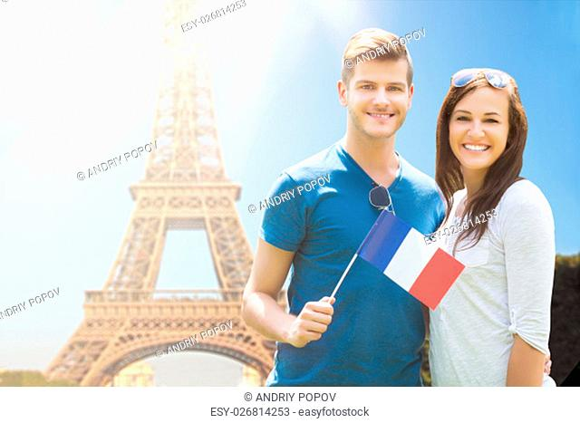 Happy Couple Holding French Flag In Front Of Eiffel Tower