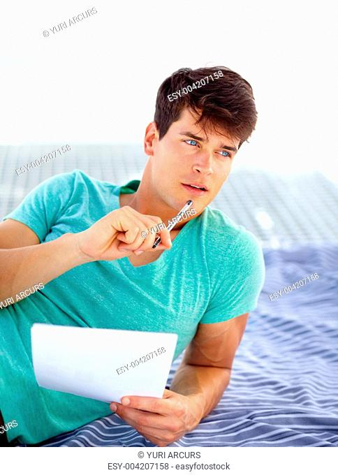 Young man brainstorming holding a pen and sheets of paper in his hands