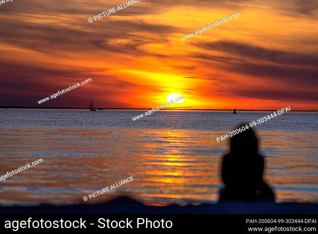 02 June 2020, Mecklenburg-Western Pomerania, Timmendorf (poel): A vacationer sits on the beach on the island of Poel and watches the sunset
