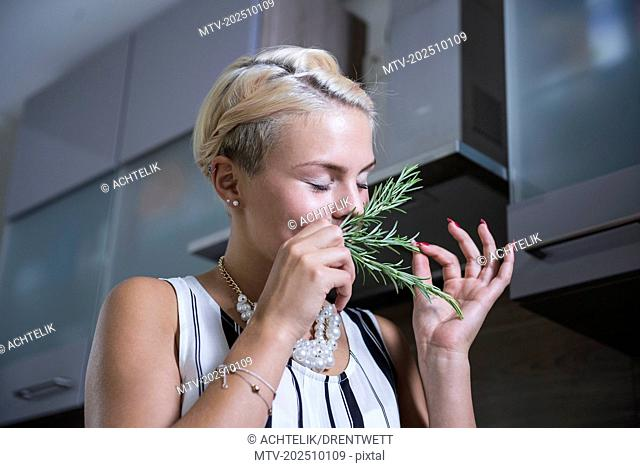 Young woman smelling rosemary in the kitchen, Bavaria, Germany