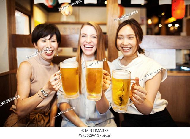 Three women sitting sidy by side at a table in a restaurant, holding large glasses with beer