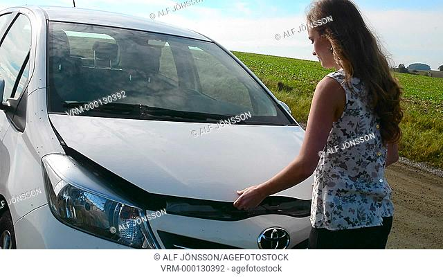 Young woman control the engine on her car